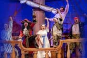 Actors performing as characters from Peter Pan on a boat set.